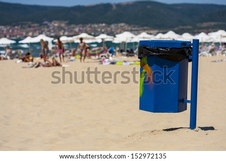 Blue trash basket with graffitii on the beach. - stock photo