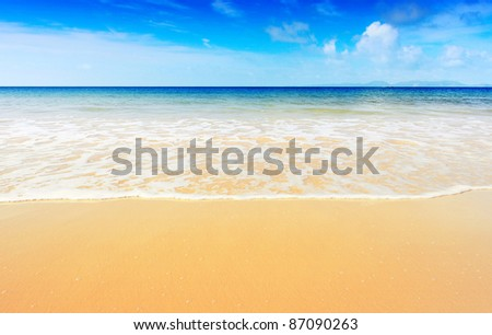 Blue tropical sea with sky and clouds on a horizon and yellow sandy beach - stock photo