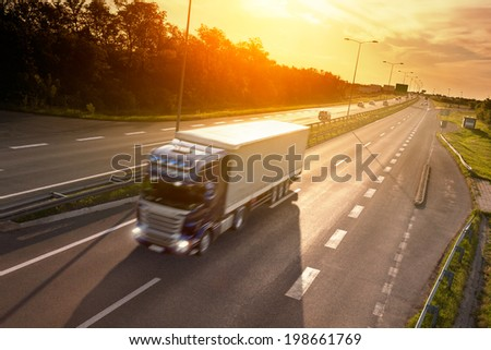 Blue truck in motion blur on the highway at sunset - stock photo