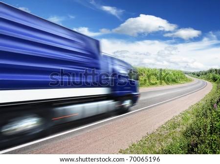 blue truck speeding on country highway, motion blur - stock photo