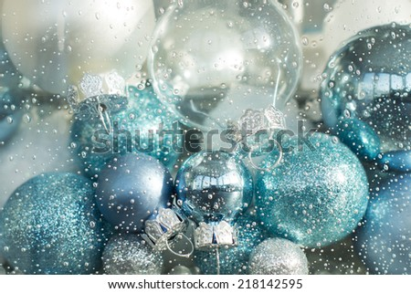 blue, turquoise and white christmas balls in a decorative glass - stock photo