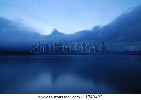 blue twilight photo of mountain lake in Japan with moving clouds and still water, Nikko, Japan