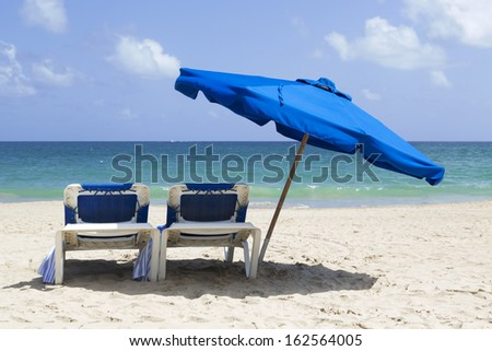 blue umbrella and two chairs on a pristine white sandy beach - stock photo