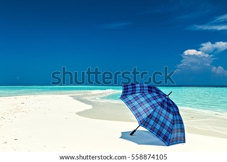 Blue umbrella is on a coral sandy beach, Maldives, The Indian Ocean