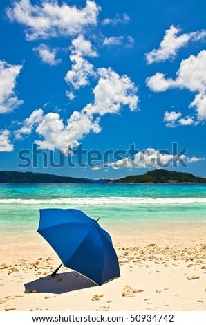 Blue umbrella is on a sandy beach, Seychelles - stock photo