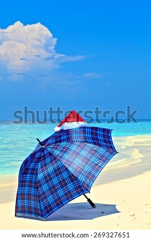 Blue umbrella is on a sandy beach with Santa Hat - stock photo