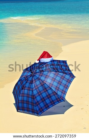 Blue umbrella is on a sandy beach with Santa Hat
