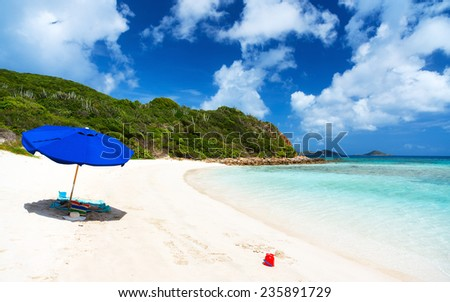 Blue umbrella on picture perfect beach with white sand, turquoise ocean water and blue sky at tropical island in Caribbean - stock photo