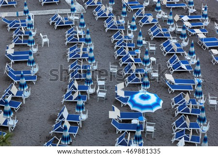 Blue umbrellas and chaise longue on empty sandy beach, Amalfi, Italy, Europe