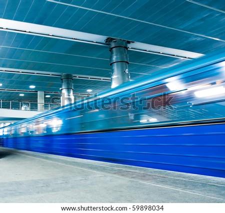 blue underground platform with moving train - stock photo