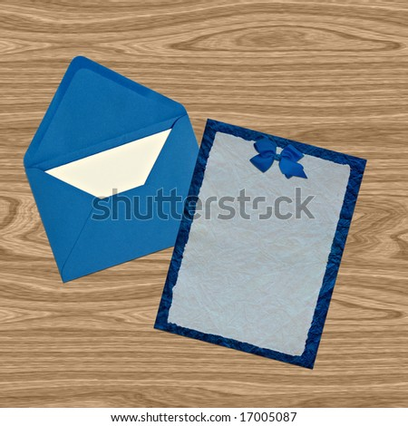 Blue vellum invitation and envelope on wooden background - stock photo