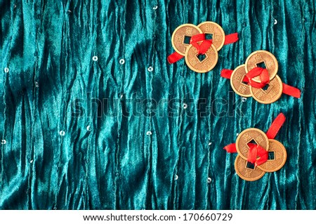 Blue velvet background with nine Chinese lucky coins - stock photo