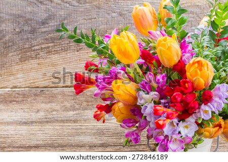 blue, violet  and red freesia and orange tulip flowers  close up on wooden background - stock photo