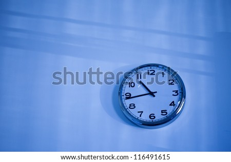 blue wall clock and blue shadows - stock photo