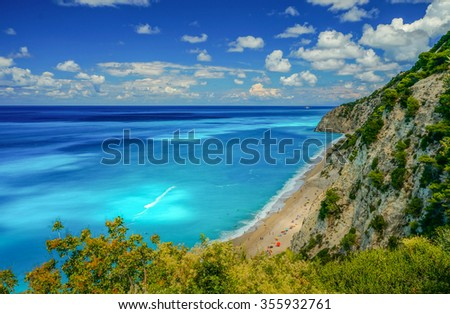 Blue water beach by a cliff in Greece