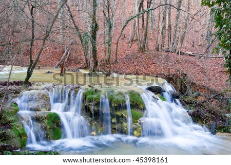 blue water cascade on a forest river - stock photo
