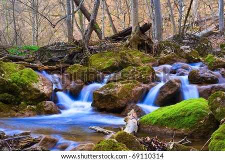 blue water cascades on a mountain river - stock photo