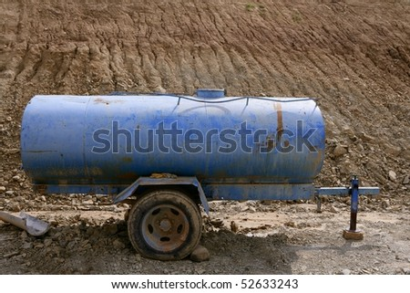 Blue water container trailer to wet soil in roads construction - stock photo