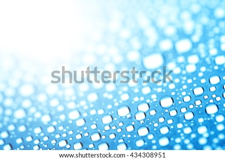 Blue water drops on treat water-repellent surface in macro lens shot small-DOF for screen wallpapers - stock photo