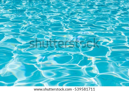 Blue water in swimming pool with sun reflection