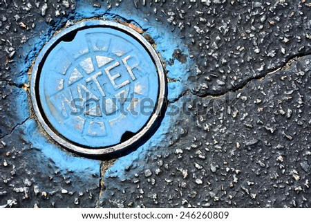 Blue water main on asphalt  - stock photo