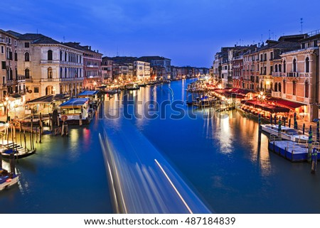 Blue water of Venice Grand Canal from Rialto bridge at sunset when nearby palaces, cafes and services are illuminated.