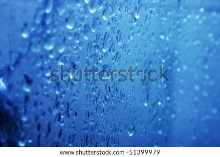 Blue water  on glass with bubbles as a background. - stock photo