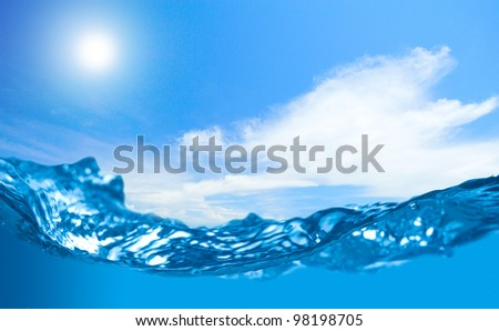 Blue water wave with shallow depth rise and cloudy sky with sun in the background - stock photo