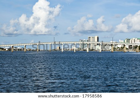 Blue waters below a bridge lined with condo's in the background. - stock photo