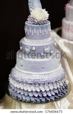 Blue wedding cake decorated with flowers and pearls - stock photo
