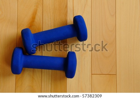 Blue Weights on Hardwood Floor of Fitness Center, view from above, copy space - stock photo
