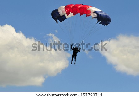 Blue white and red sail parachute on blue sky with white clouds.