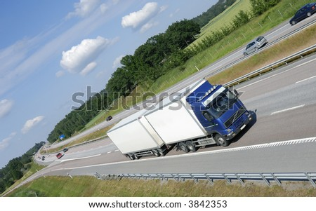 blue white truck driving on highway - stock photo