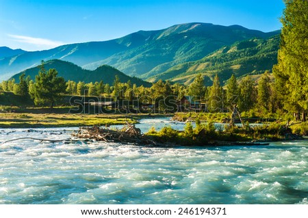 Blue wide river flowing in front of the house in the mountains - stock photo