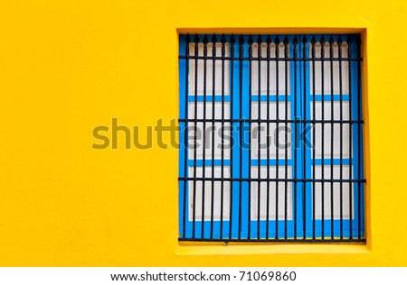 Blue window on a bright yellow wall with copyspace - stock photo