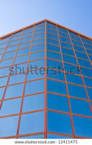 Blue windows from office building against blue sky.