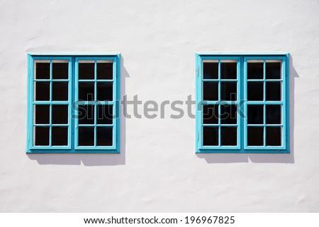Blue windows on the wall - stock photo