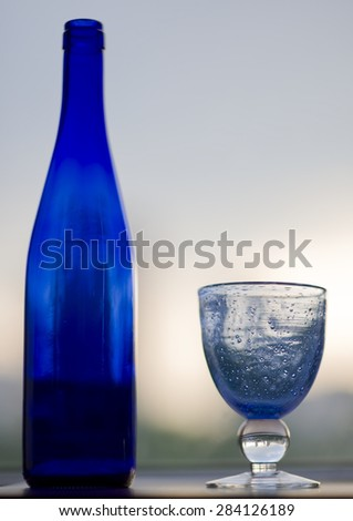 blue wine bottle and wine glass blue on a white background - stock photo