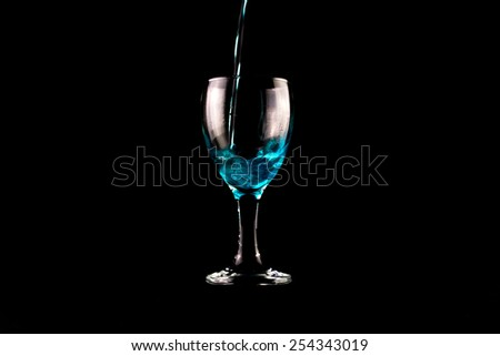 Blue wine glass on black background - stock photo