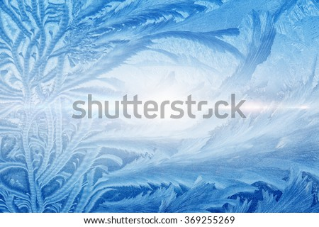 Blue winter background - frozen icy window glass, icy pattern looks like fir branch - stock photo
