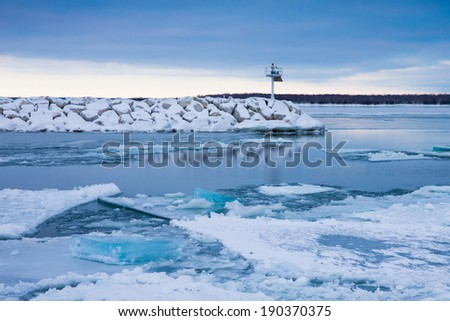 Blue Winter Ice - winter scene with blue ice and breakwater.  Lake Michigan at Northport Pier in Door County, Wisconsin.  Copy space at top. - stock photo