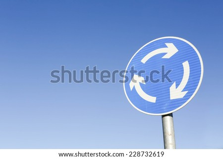 Blue with white arrows roundabout road traffic sign ahead against a blue sky background - stock photo