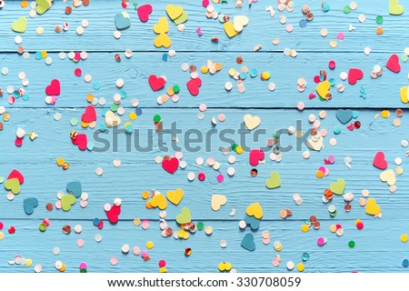 Blue wood background with scattered colorful party confetti with heart shapes in a closeup full frame overhead view for festive or celebration themed concepts - stock photo