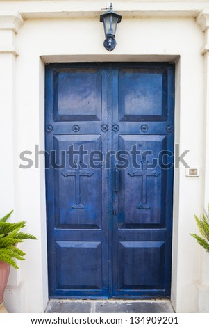 Blue wood church door wit a lamp and crucifix
