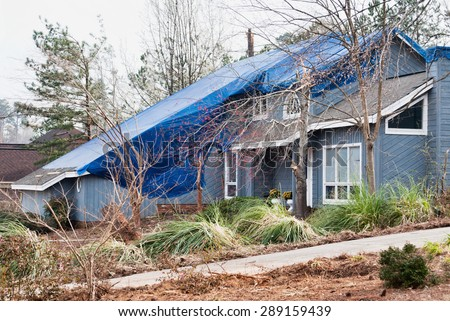Blue wood framed house with a large blue tarpaulin covering the roof after an EF2 tornado came through this residential neighborhood in March. Trees are broken and the yard is destroyed.  - stock photo