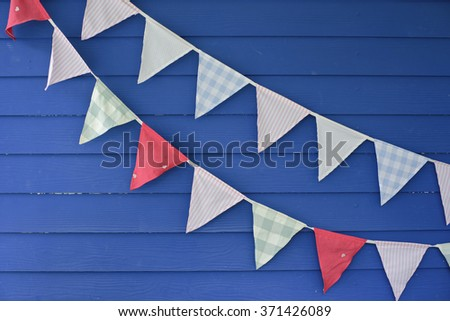 blue wood pattern with pastel triangle flags  - stock photo