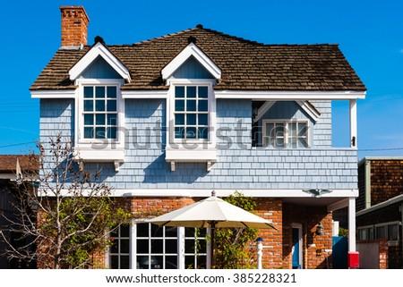 blue wood shingle and brick house  - stock photo