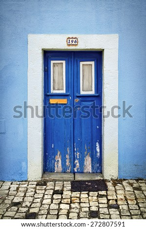 Blue wooden door in the facade of a typical Portuguese house - stock photo