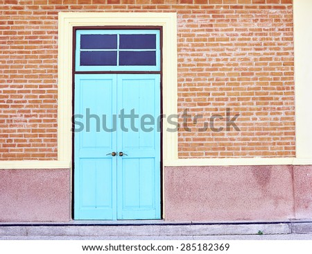 Blue wooden door on a brick wall. - stock photo