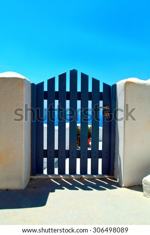 blue wooden gate in white house, beautiful details of Santorini island, Greece, sunny day - stock photo